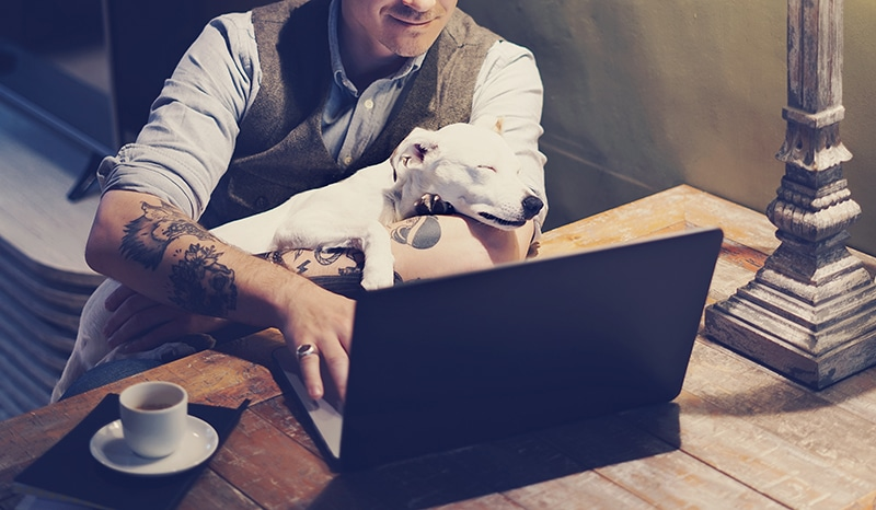 Smiling tattooed man in eyeglasses working at home on laptop while sitting at the wooden table with cute dog sleeping on his hands.Adult guy using modern computer for surfing web.Horizontal.