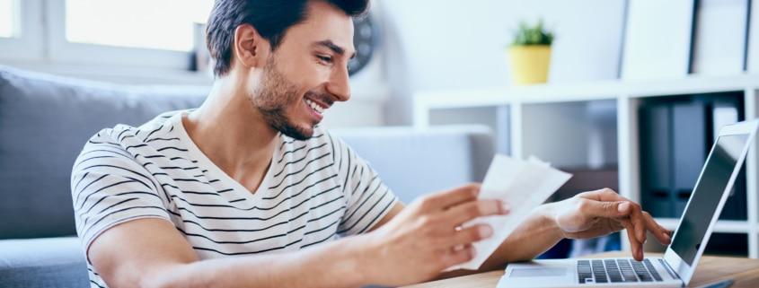 Happy man filing his online tax return